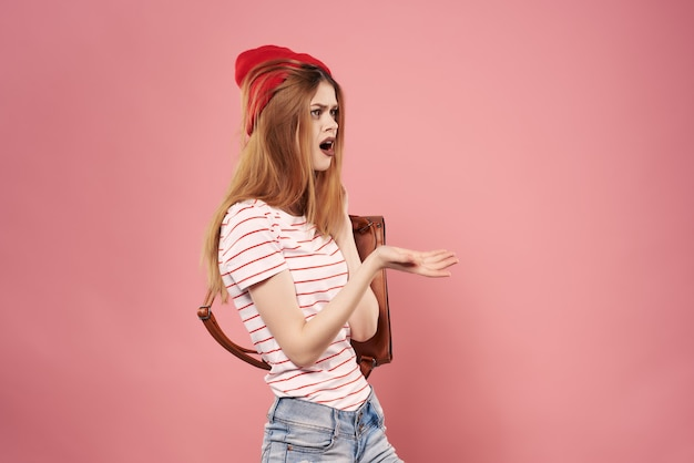 ファッションをポーズする手で赤い帽子のバックパックでファッショナブルな女性。高品質の写真