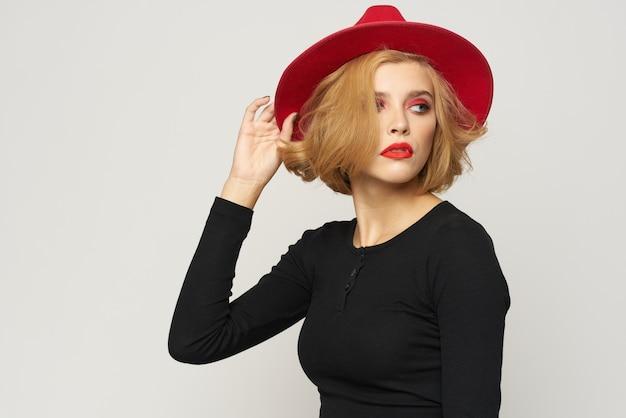Модная женщина в красной шляпе, черная блузка, красные губы, обрезанные, вид легких эмоций.