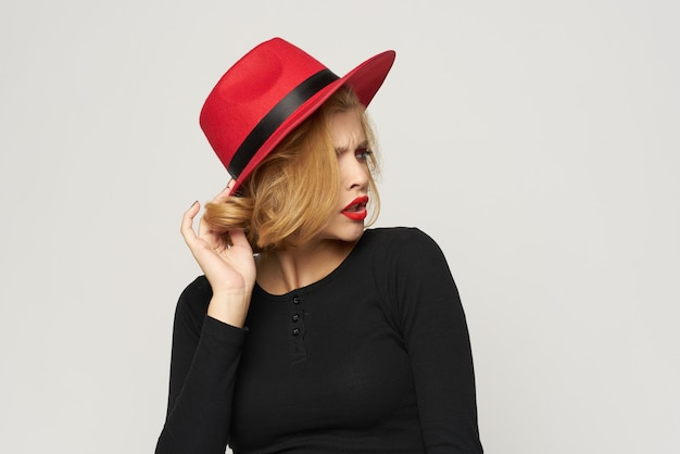 赤い帽子の黒いブラウスの赤い唇でファッショナブルな女性は、光の感情をトリミングしました。