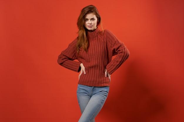 赤いセーターとジーンズのカジュアルな服装でファッショナブルな女性が孤立した背景をポーズ