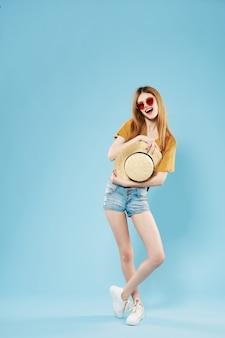 夏服を着たファッショナブルな女性は、青い背景をポーズフルレングス立っています