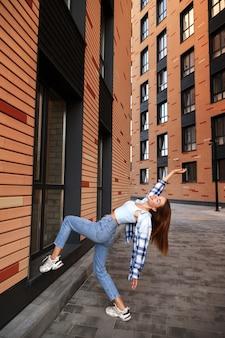 Модная женщина в городе среди модных зданий позируют.