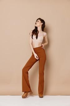 Модная женщина в брюках, футболке и туфлях на высоких каблуках на бежевом фоне жестикулирует руками. фото высокого качества