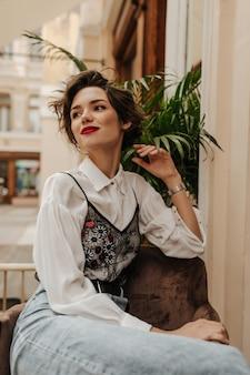흰 블라우스와 청바지 카페에서 웃 고있는 유행 여자. 레스토랑에 앉아 짧은 갈색 머리를 가진 유행 여자.