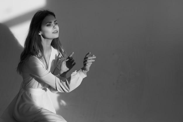 豪華なスタジオをポーズする白いドレスの魅力のファッショナブルな女性。高品質の写真