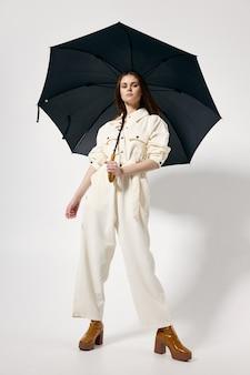 白いジャンプスーツのファッショナブルな女性は、フルレングスの傘のファッションブーツを開きます。