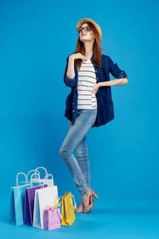 ファッショナブルな女性が青色の背景にパッケージで買い物