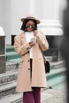Fashionable woman looking on her phone outside