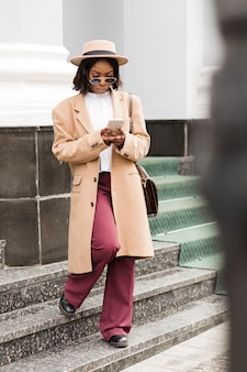 Fashionable woman looking on her phone