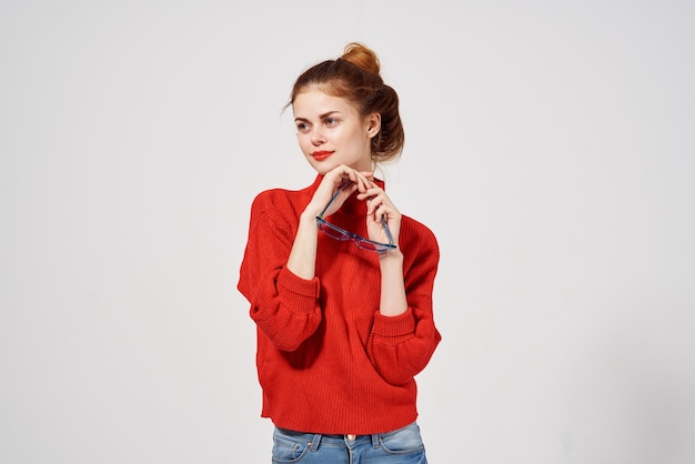 赤いセーターと青いメガネのファッショナブルな女性モデル