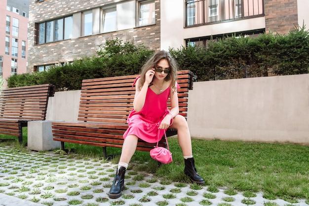 가방을 들고 핑크색 드레스를 입고 벤치에 앉아 포즈를 취하는 세련된 여성 모델
