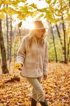 秋の公園の屋外でファッショナブルな女性