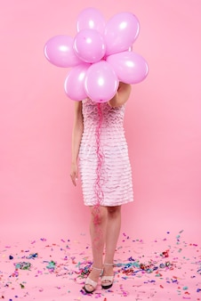 Fashionable woman at party holding balloons