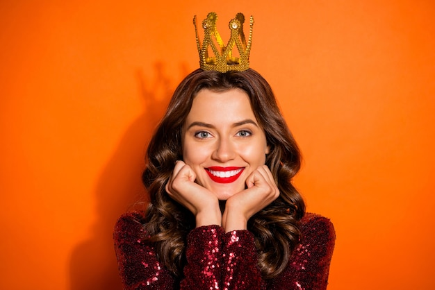 Fashionable woman posing against the orange wall
