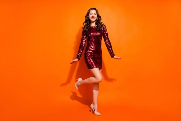 Модная женщина позирует у оранжевой стены