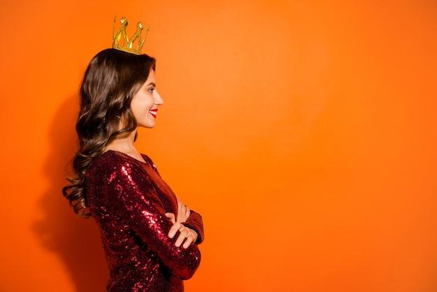 オレンジ色の壁にポーズをとるファッショナブルな女性