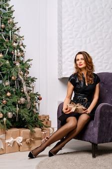 크리스마스 트리와 벽난로 근처 안락의 자에서 포즈 유행 여자, 구식 스타킹 다리를 보여주는