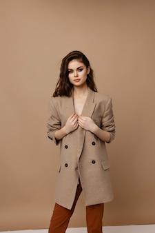 コートとズボンのベージュの背景にポーズをとるファッショナブルな女性。高品質の写真