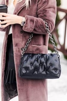 Модная женщина позирует на улице в модной искусственной коричневой шубе, с черной сумочкой и стаканом горячего напитка в руках. фото
