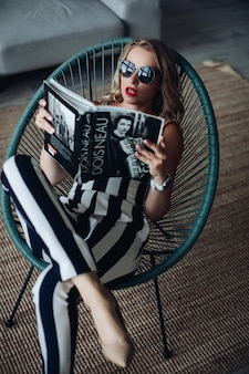 Fashionable woman reading magazine in chair.
