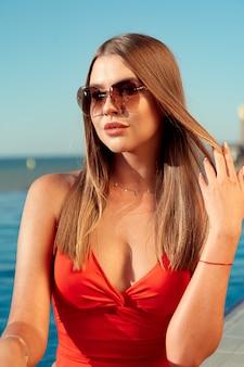 Fashionable woman in red bikini sitting near the pool