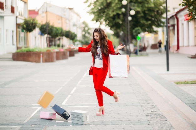 Fashionable woman in red suit with shopping bags dropped shoe boxes in the street.