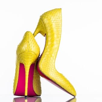 白い背景で隔離のファッショナブルな女性のハイヒールの靴。美しい黄色の女性のハイヒールの靴。贅沢。背面図