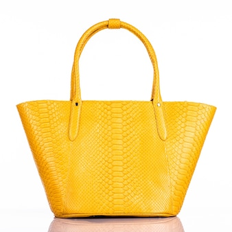 白い背景で隔離のファッショナブルな女性のスタイリッシュなバッグ。美しい紫色の高級革の女性のハンドバッグ。高級アクセサリー。