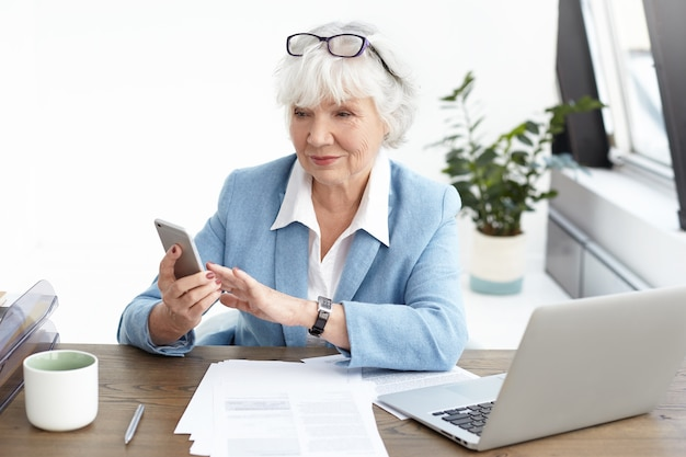Fashionable woman senior architect with gray hair and eyeglasses on her head surfing internet or typing text message via smart phone, working at office desk, sitting in front of open laptop