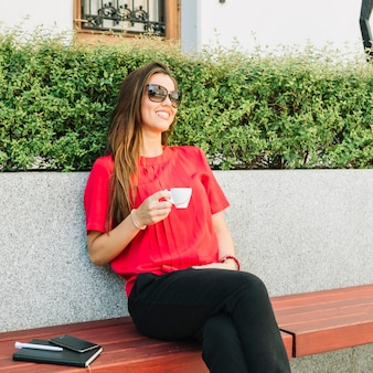 Fashionable woman sitting on bench drinking coffee