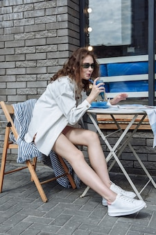 카페에 앉아 칵테일을 마시는 세련된 여성
