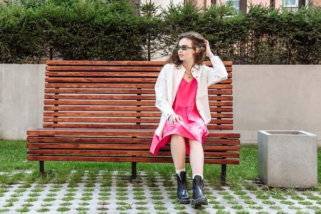 벤치에 앉아 세련된 옷 카탈로그에서 포즈를 취하는 세련된 여성