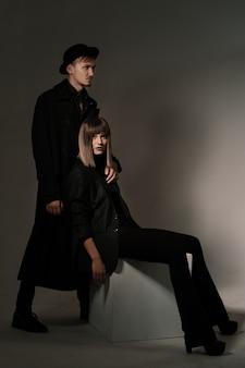 남자가 그녀의 뒤에 서있는 동안 유행 여자는 큐브에 앉아