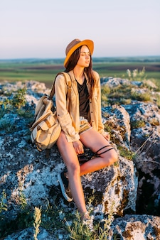 Fashionable woman sitting on rock