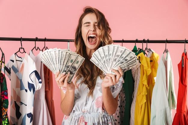 Модная женщина, стоящая возле гардероба, держа в руках денежные вентиляторы, изолированные на розовом