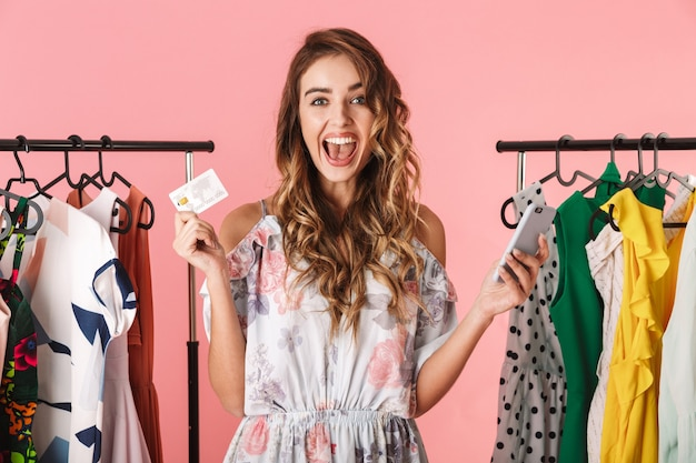 Fashionable woman standing near wardrobe while holding smartphone and credit card isolated on pink