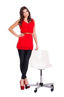 椅子の横に立っているファッショナブルな女性