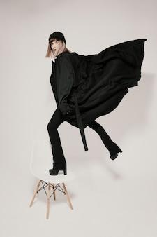 飛ぶふりをして白い椅子に立っているファッショナブルな女性