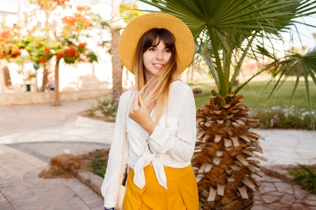 Fashionable woman standing on palms and blooming trees. wearing straw hat.
