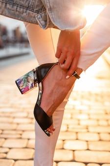 유행 여자는 일몰에 그녀의 신발을 곧게 만듭니다. 확대.