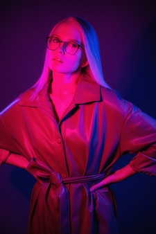 Fashionable woman in stylish trench coat and glasses posing in neon light stylish model in colored l...