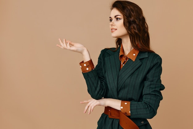 Fashionable woman in suit shows with hand towards