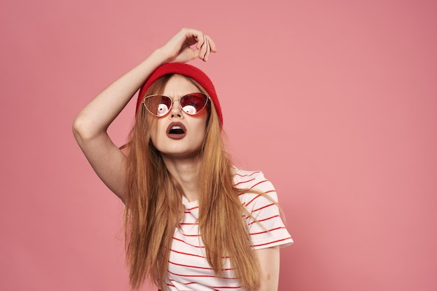 Fashionable woman sunglasses and red hat studio pink background fashion
