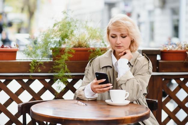 屋外カフェで電話で話すファッショナブルな女性