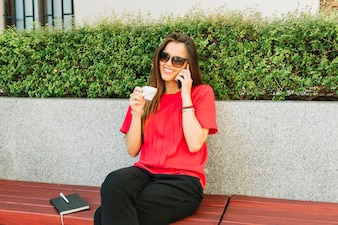 Fashionable woman talking on cellphone while drinking cup of coffee