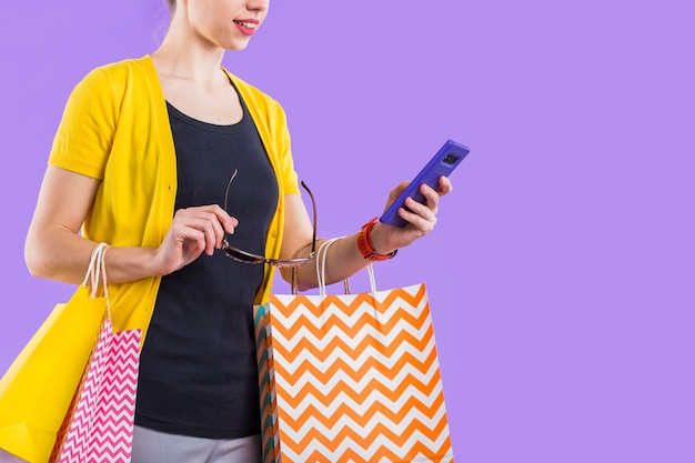 Fashionable woman using cellphone with holding colorful paper bag and eyeglasses