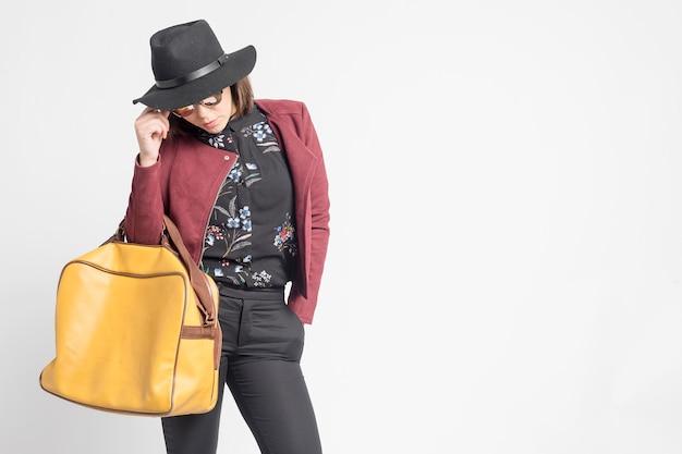 Fashionable woman wearing hat, sunglasses and handbag