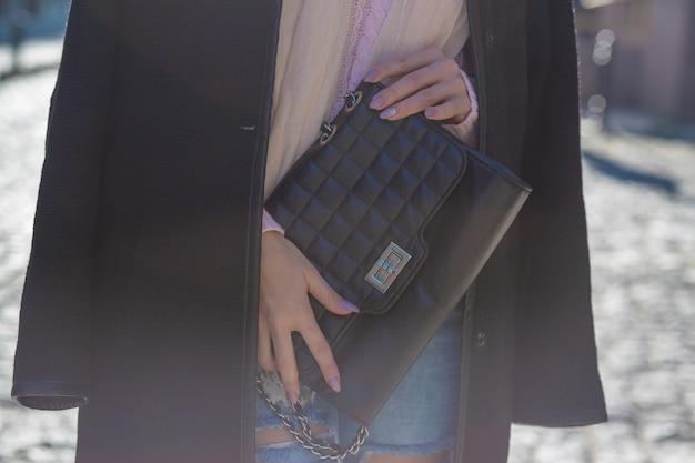 スタイリッシュなコート、熟したジーンズ、黒い革の財布を持ったセーターを着ているファッショナブルな女性。クローズアップショット