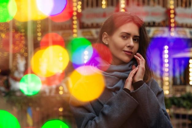 ファッショナブルな女性は、ボケの光で通りを歩いている灰色のコートを着ています。空きスペース