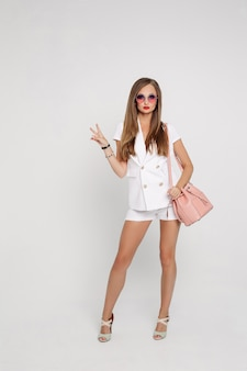 Fashionable woman in white suite showing peace.